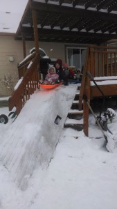 Kids sledding off the deck